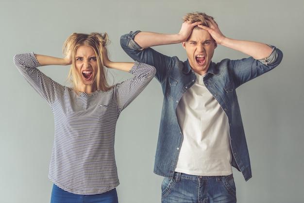 美しい若いカップルは髪を乱しています。