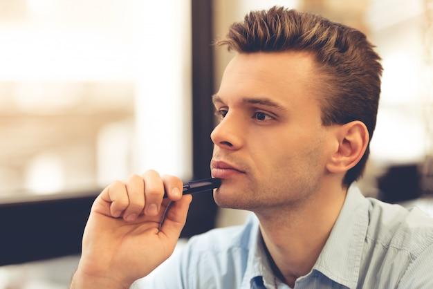 ハンサムな物思いにふける青年実業家は、ペンを持っています。