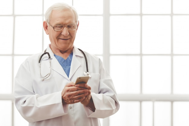 白い医療コートの医者は、スマートフォンを使用しています。