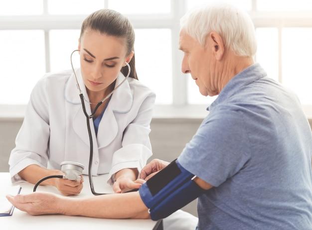 医療コートの医者は患者の血圧をテストしています。