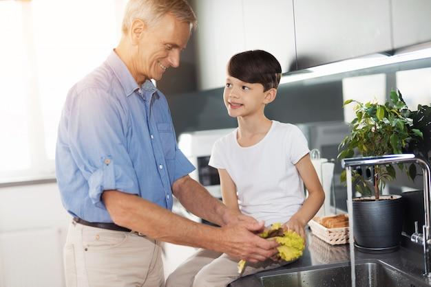 青いシャツを着た男が台所の流しのそばに立っています。