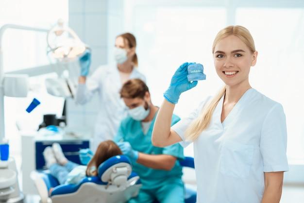看護師は義歯であごの模型を握る。看護師の笑顔