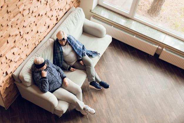 Пожилые женщины отдыхают на диване после гимнастики.