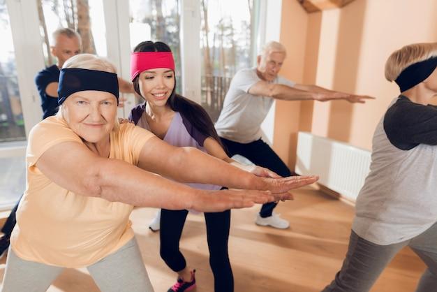 Пожилые женщины и молодой инструктор занимаются вместе.