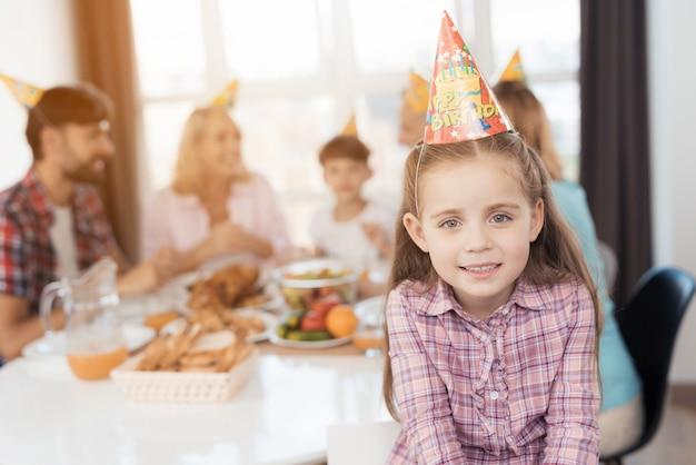 女の子は笑みを浮かべて、彼女の誕生日のお祝い帽子でポーズをとっています。