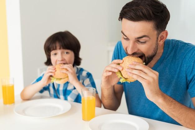 父と息子はジュースでハンバーガーを食べています。