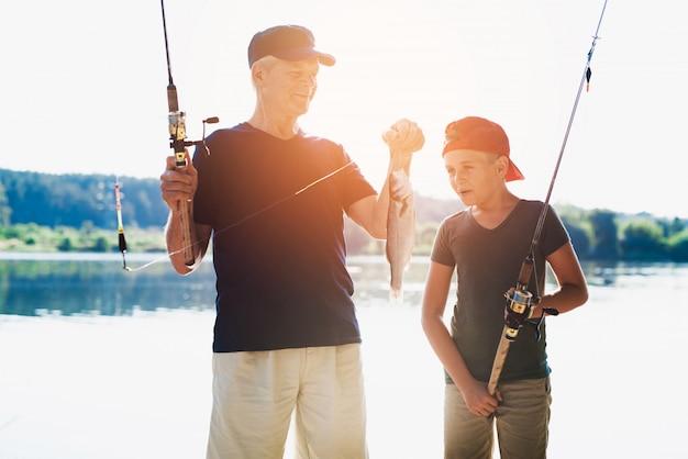 Счастливый дедушка и внук ловят рыбу на реке.
