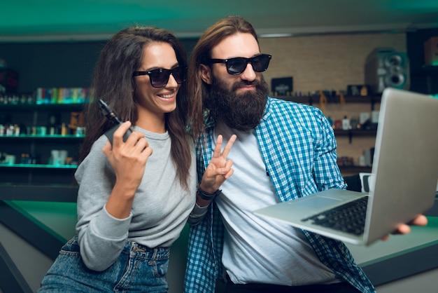男と女は気化器とラップトップで座っています。