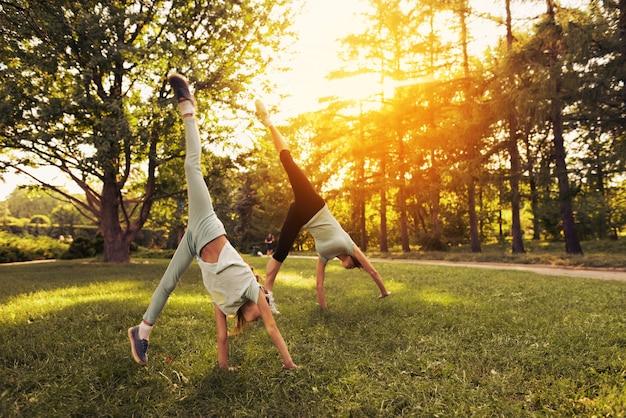 公園でフィットネス。女性と娘は逆立ちをします。