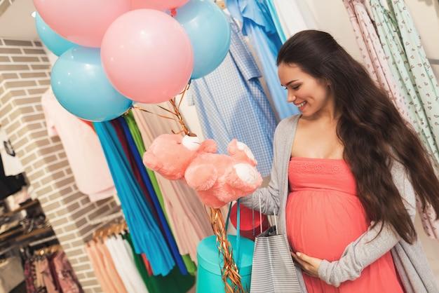 妊娠中の女性が店でベビー用品を選びます。