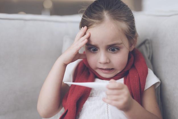 家で座っている熱を持つ少女。