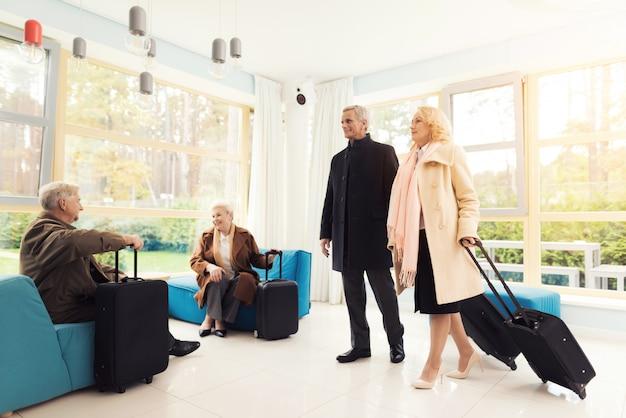 Пожилая пара в приемной с чемоданами.