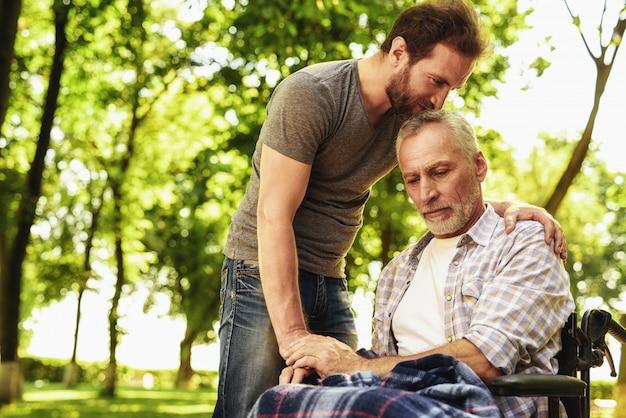 Сын поцелуй голову старика. реабилитация на открытом воздухе.