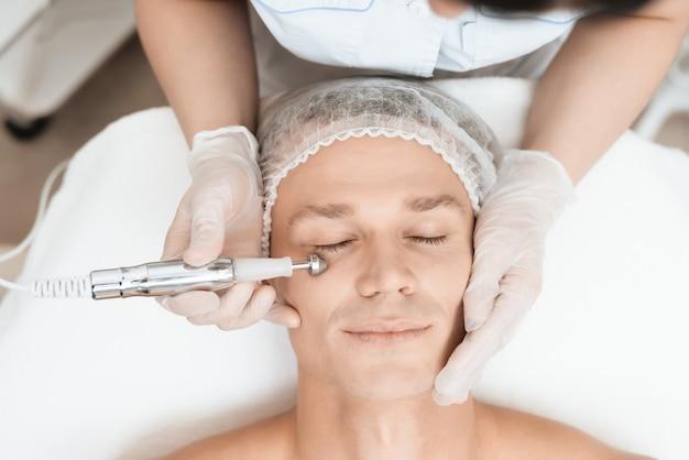 医者は現代のレーザー脱毛器で彼を顔に導きます。