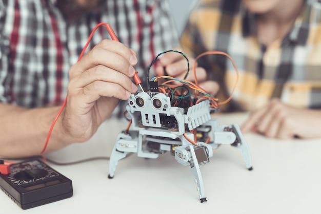 Бородатый отец и сын строит робот у себя дома.