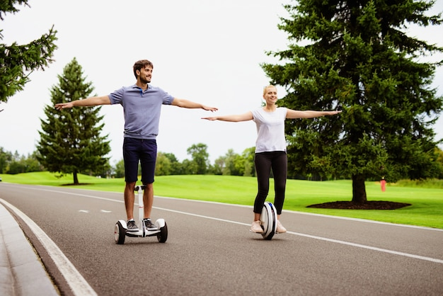 カップルは公園でジャイロボードとモノクルに乗っています。
