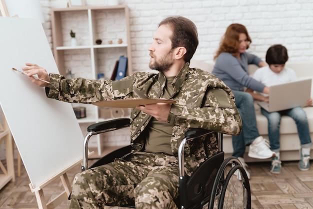 車椅子のベテランは彼の手にペンキとブラシを持っています。