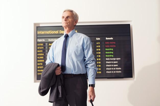 スーツを着た老人が空港に立っています。