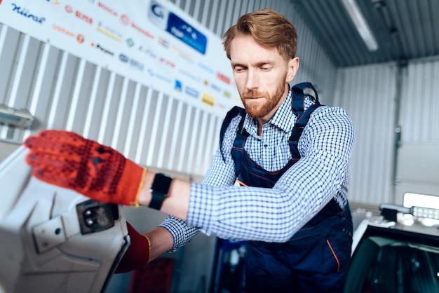 男性整備士が装置を固定する仕事をします。