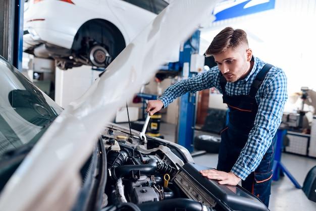 Молодой автомеханик ремонтирует автомобиль с помощью гаечного ключа.