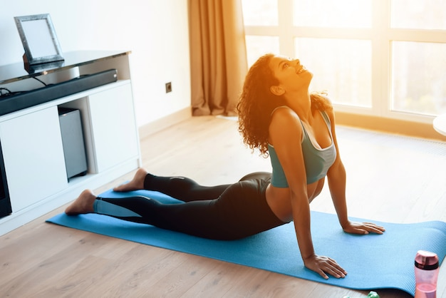 Красивая африканская девушка делает упражнения йоги на коврик для йоги