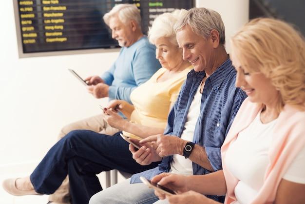 Пожилые люди сидят в зале ожидания в аэропорту.