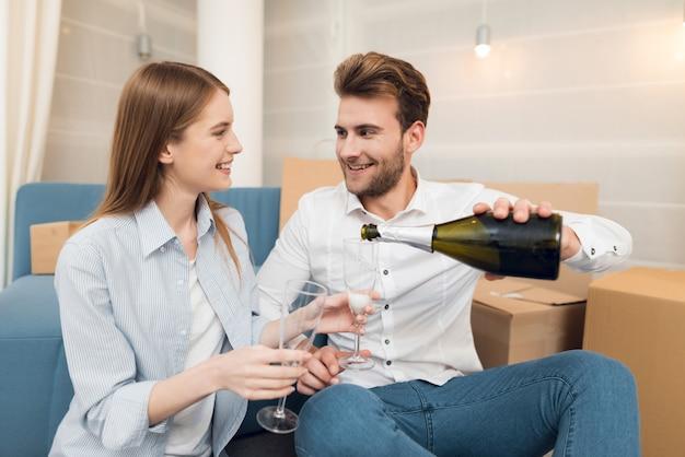 カップルは新しいアパートに移動シャンパンで祝っています。