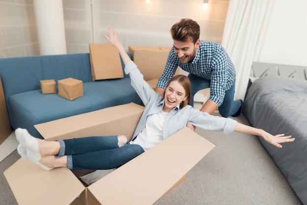 Молодая пара весело при переезде в новую квартиру.