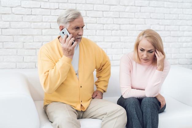 黄色いカーディガンの男が彼のスマートフォンで話しています。