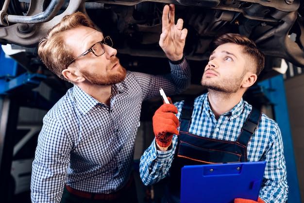 Клиент и механик проверяют детали автомобиля.