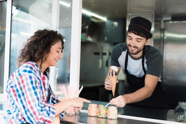 シャツを着た女性がフードトラックでアイスクリームを購入します。