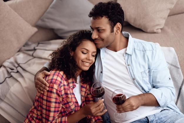 アフロアメリカンのカップルはロマンチックなデートにワインを飲みます。