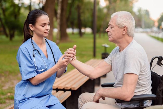 看護師が高齢患者の手首を診察します。