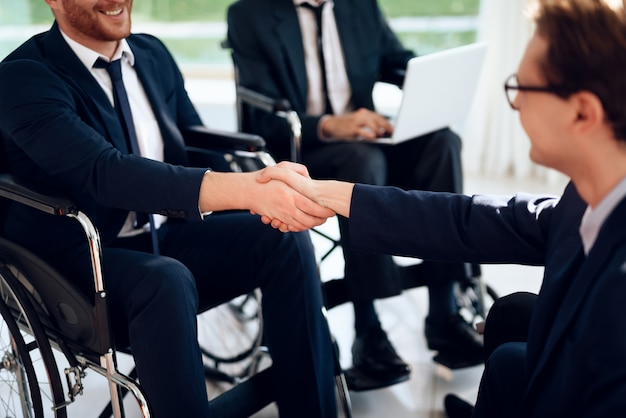 ビジネスの障害者は明るい部屋でスーツを着ます。