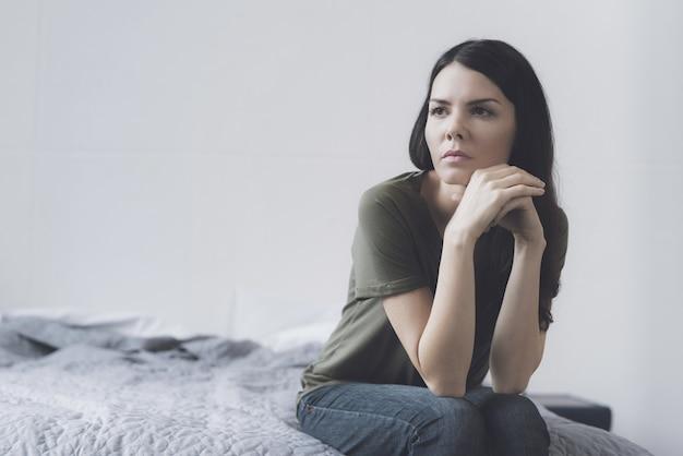 Портрет грустной темноволосой женщины сидит на кровати