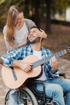 公園でギターを弾く車椅子の男。