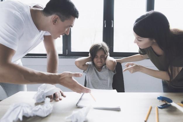 怒っている両親は宿題をしながら女の子で叫ぶ