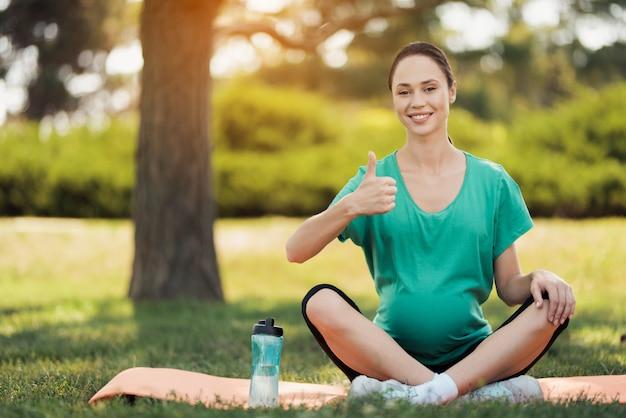 Беременная женщина в зеленой футболке сидит на ковер для йоги.