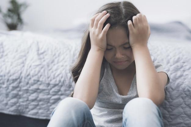 泣いて動揺の小さな女の子が室内の床に座る