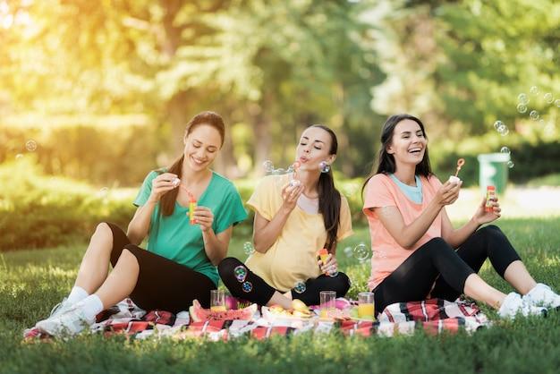 妊娠中の女性は公園でシャボン玉を吹いています。