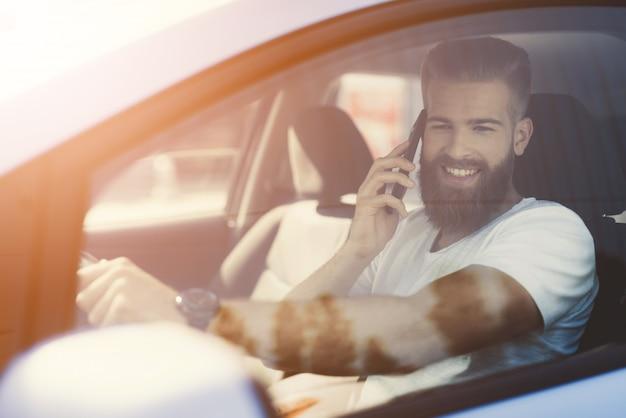 Мужчина с бородой садится за руль электромобиля.