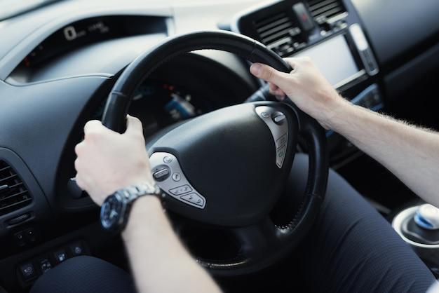 男は車のハンドルを握ります。