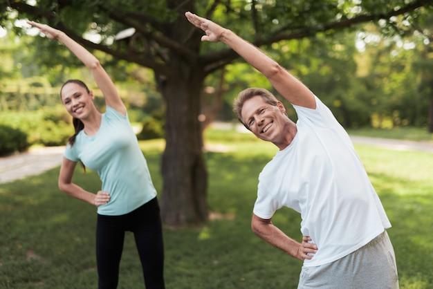 Мужчина и женщина делают упражнения в парке.