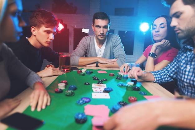 Молодые люди играют в покер за столом.