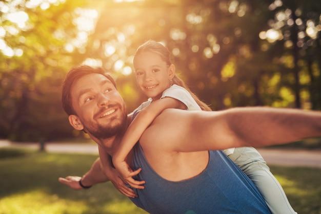男が公園の彼の肩に女の子を乗っています。
