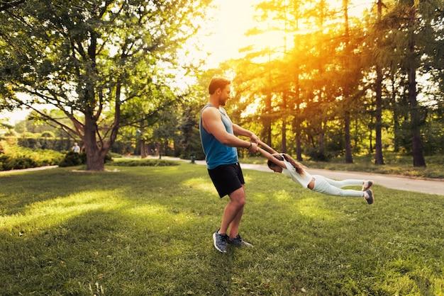 Человек с дочерью дурачится в парке.