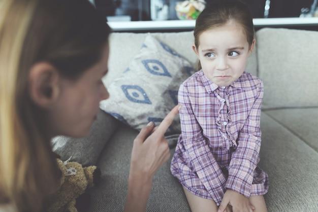 女性は女の子を罰して彼女の指をしかめます。