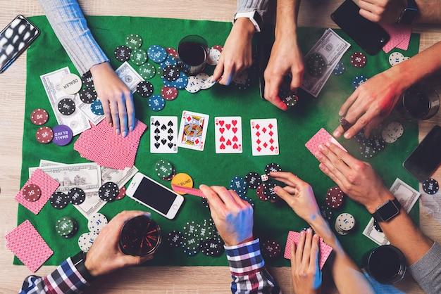 Люди играют в покер, на столе лежат карты и фишки.