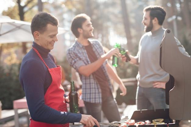 男が外でバーベキュー料理を作っています。
