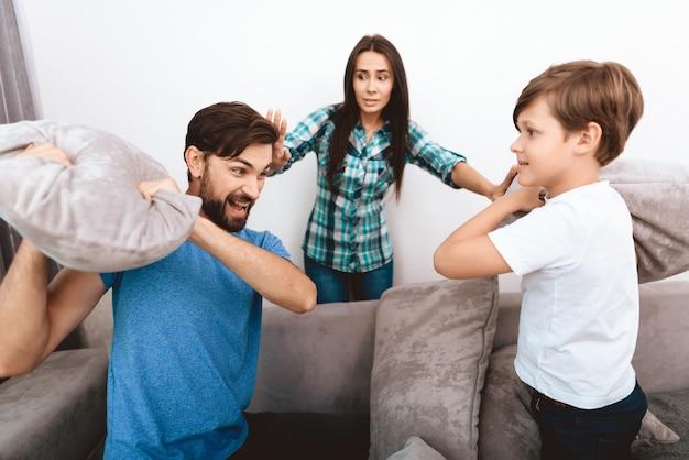 若い母親は、大人の夫と息子を落ち着かせようとします。